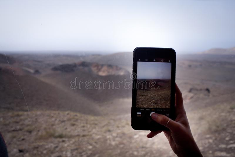 Handen tar bilder, whit somsmartphonen i timanfaya parkerar royaltyfria bilder