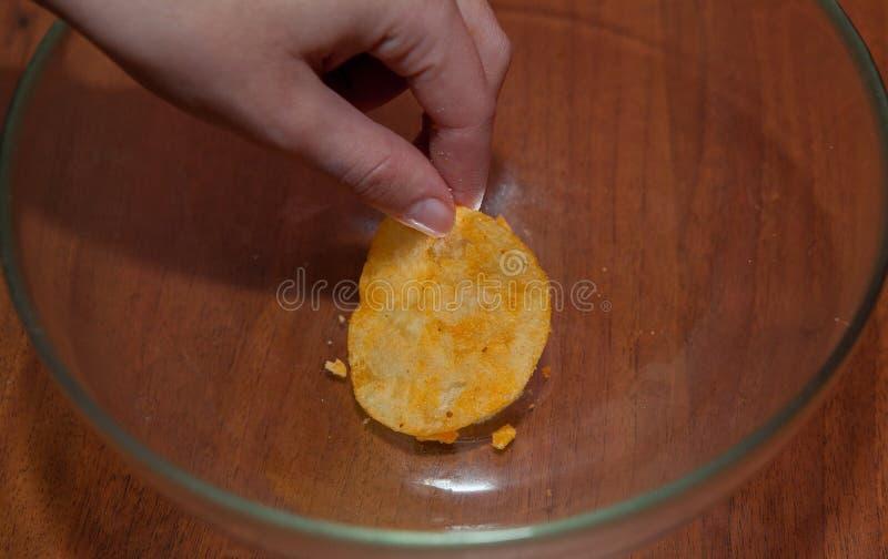 Handen tar chiperna i plattan royaltyfri bild