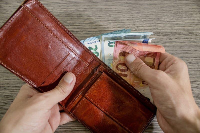 Handen tar eurosedeln från en plånbok royaltyfri bild