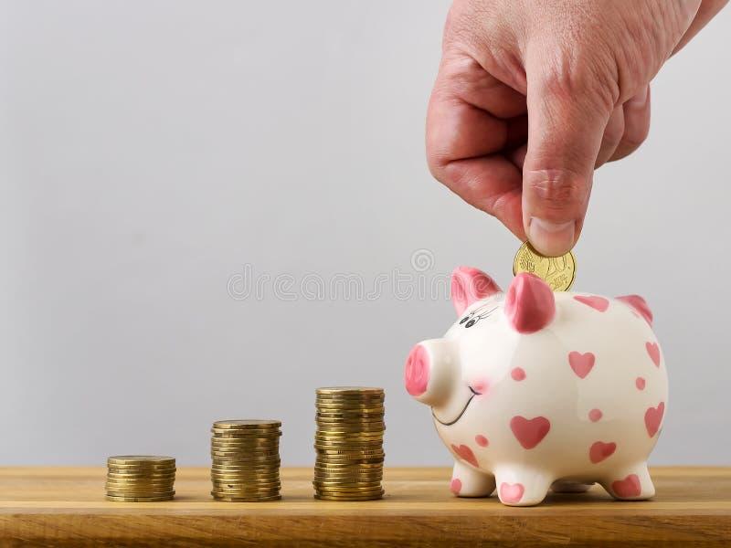 Handen tillfogar myntet till myntasken som sparar pengar kopiera avstånd arkivbild
