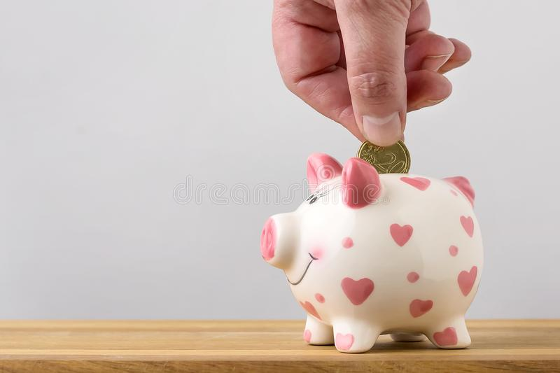 Handen tillfogar myntet till myntasken som sparar pengar kopiera avstånd royaltyfri bild
