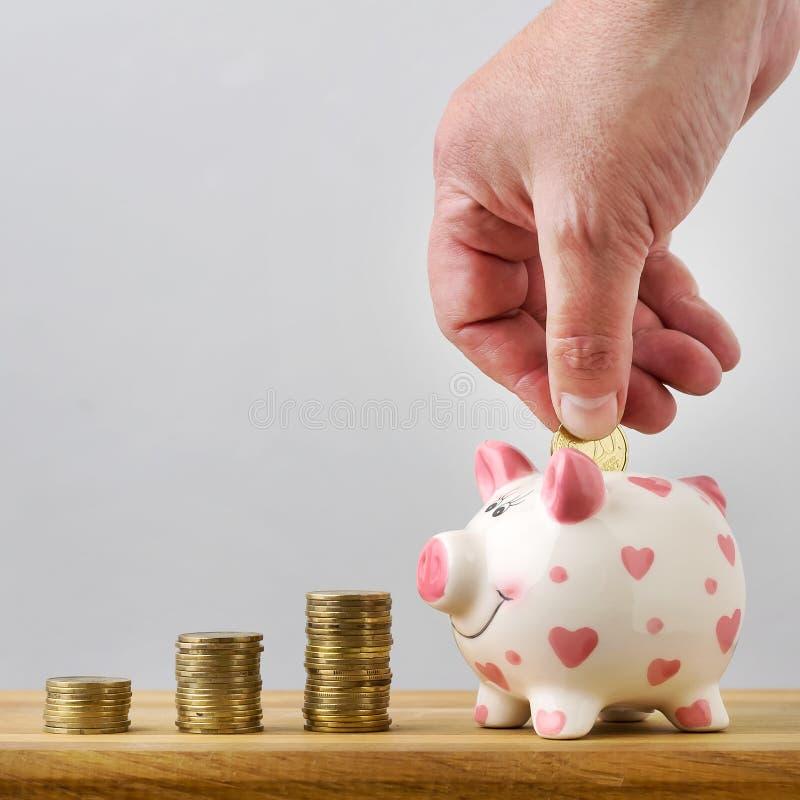 Handen tillfogar myntet till myntasken som sparar pengar kopiera avstånd arkivfoton