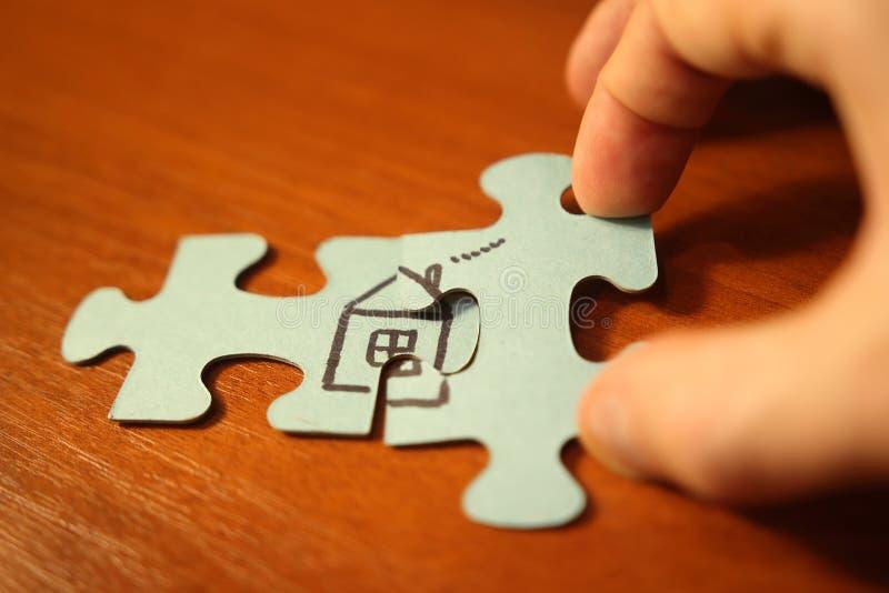 Handen tillfogar pusselstycken till huscloseupen Byggandehusbegrepp Hem- komfort och förälskelse fotografering för bildbyråer