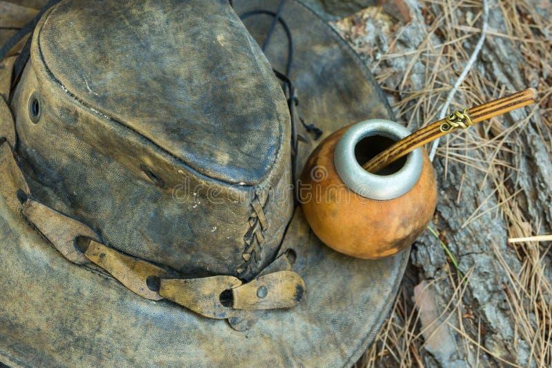 Handen tillverkade Artisanal Yerba Mate Tea Leather Calabash Gourd med Straw Hat på trä loggar in Forest Travel Wanderlust Concep royaltyfria foton