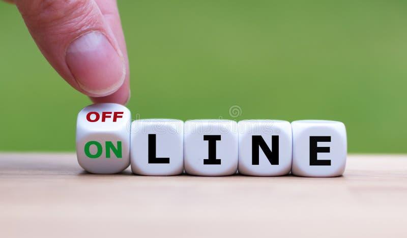 Handen vänder tärning och ändrar 'det offline-'ordet till 'online- ', royaltyfri fotografi
