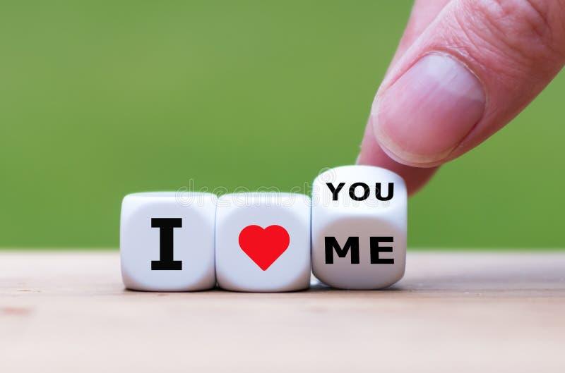 Handen vänder tärning och ändrar uttryckt, 'som jag älskar mig 'till 'mig älskar dig ', arkivbild