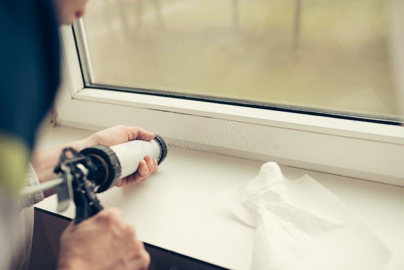 Handen van arbeider die een siliconebuis voor het herstellen van venster met behulp van stock fotografie