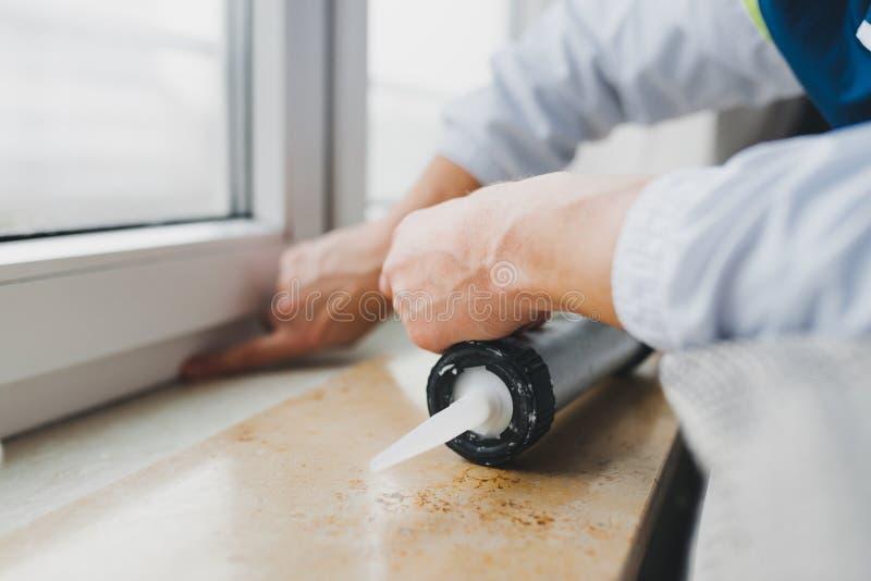 Handen van arbeider die een siliconebuis voor het herstellen van venster met behulp van stock foto