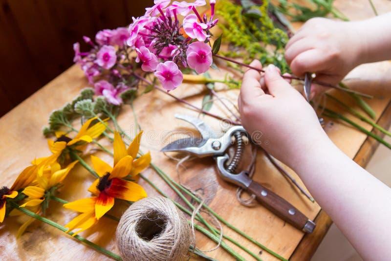 Handen van bloemist die bloemenboeket maken Hobbyconcept stock afbeeldingen
