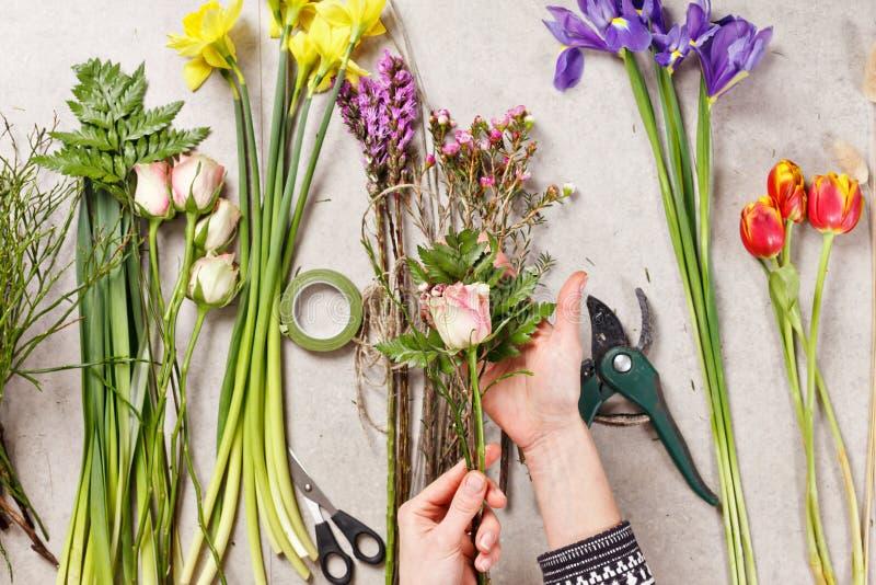 Handen van bloemist die boeket maken bloemen opspringen stock foto