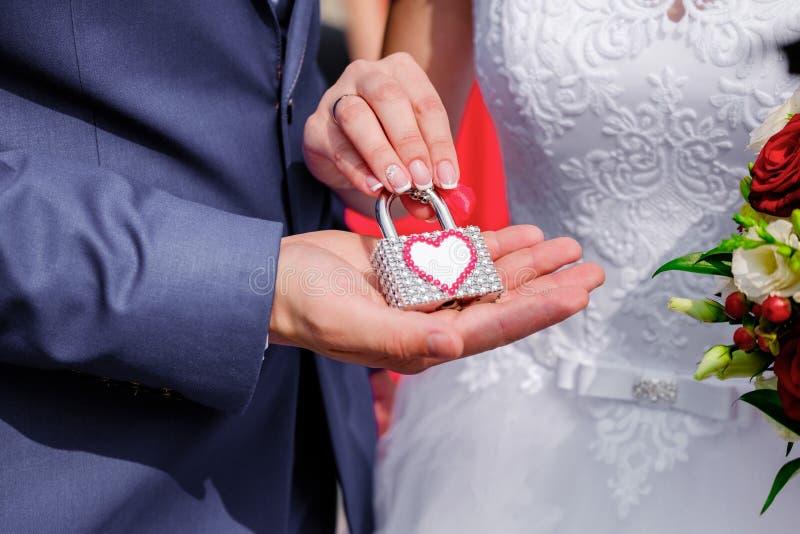 Handen van bruid en bruidegom met uitstekend slot royalty-vrije stock afbeeldingen