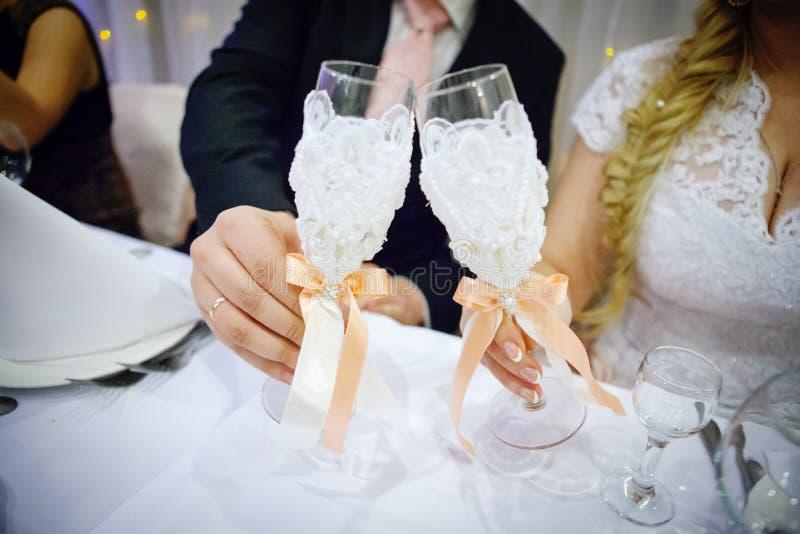 Handen van bruid en bruidegomgerinkelglazen met champagne royalty-vrije stock fotografie