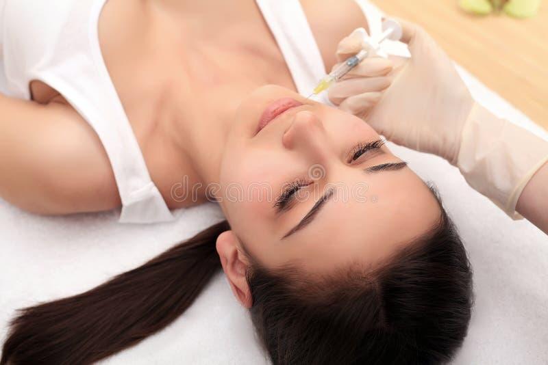 Handen van cosmetologist die injectie in gezicht, lippen maken Jonge wom stock foto