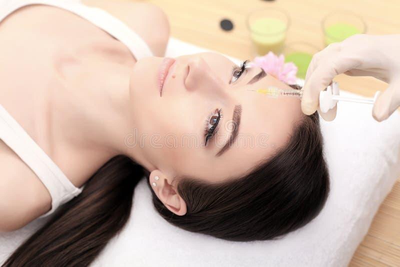 Handen van cosmetologist die injectie in gezicht maken De jonge vrouw krijgt schoonheids gezichtsinjecties in salon Gezichts het  stock afbeelding