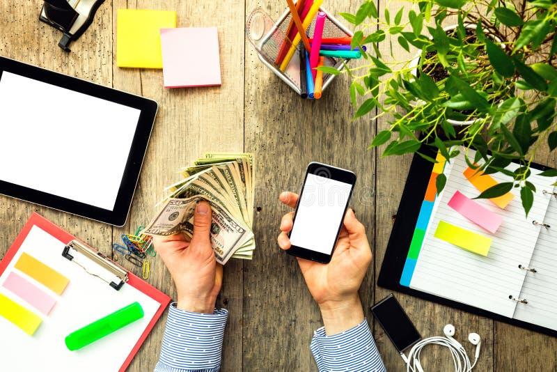 Handen van de Amerikaanse dollars en smartphone van de mensenholding stock afbeeldingen