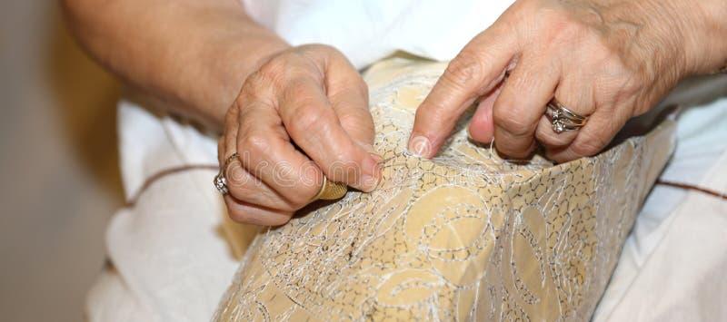 handen van de bejaarden terwijl het borduren van een kant stock foto