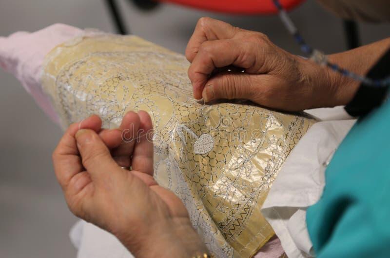 handen van de bejaarden terwijl het borduren van een kant stock foto's