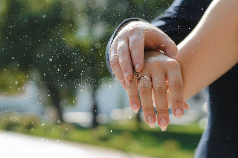 Handen van de bruid en de bruidegom met trouwringen stock afbeelding