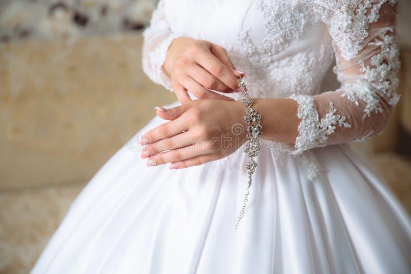 Handen van de bruid met de armband Vrouwelijke toebehoren stock afbeelding