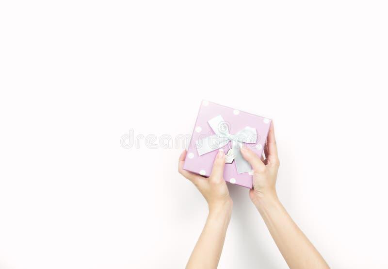 Handen van de close-up houden de mooie en gezonde vrouw met keurige manicure roze giftdoos met polka gestippeld patroon royalty-vrije stock foto's