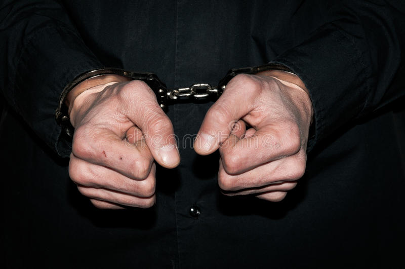 Handen van de de handboeien om:doen misdadige mens in zwart overhemd royalty-vrije stock afbeelding