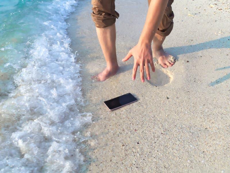Handen van de jonge Aziatische mens die mobiele slimme telefoon op tropisch zandig strand laten vallen Ongeval en van het verzeke royalty-vrije stock afbeelding