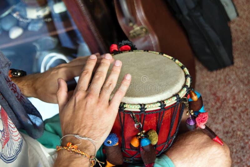 Handen van de mens die Afrikaanse trommel spelen of djembe binnen een muziekwinkel royalty-vrije stock afbeeldingen