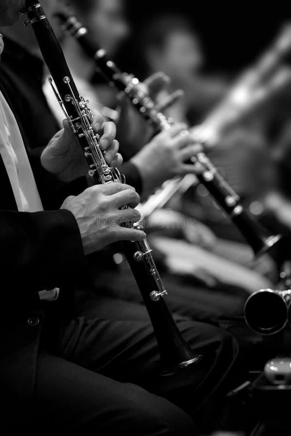 Handen van de mens die de klarinet in het orkest spelen royalty-vrije stock afbeeldingen