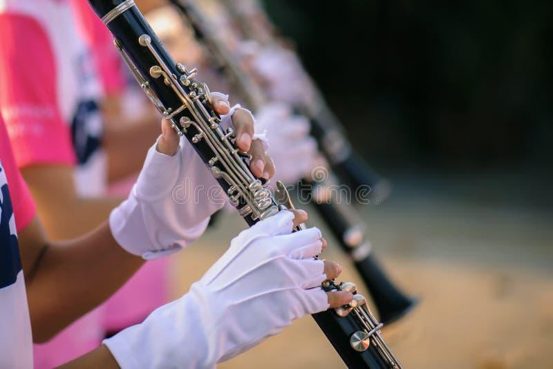 Handen van de mens die de klarinet in de het Marcheren Band spelen stock afbeelding