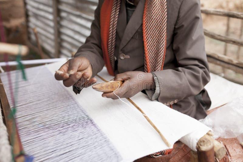 Handen van de mens op weefgetouw stock afbeeldingen