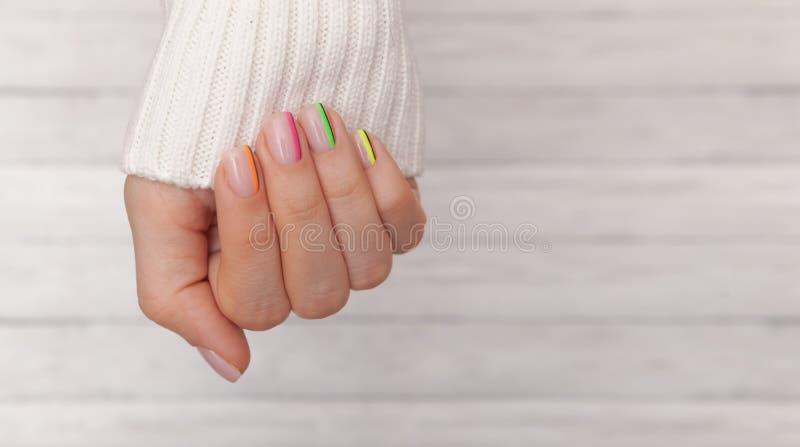 Handen van de mooie de verzorgde vrouw met gekleurde spijkers op de houten achtergrond Manicure, de salonconcept van de pedicures stock afbeeldingen