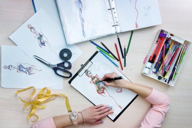 Handen van de tekeningsschetsen van de kostuumontwerper royalty-vrije stock afbeeldingen
