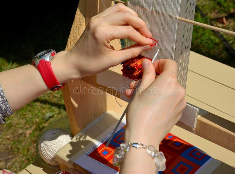 Handen van de vrouw die bij het uiterst kleine wevende weefgetouw werken Markt van nationaal stock foto