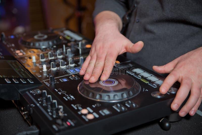 Handen van DJ ` s bij de muziekmixer bij een partij die - sommige fijne liederen voor gasten spelen stemde de kleur beeld Mooie f royalty-vrije stock foto's