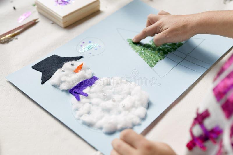 Handen van een 10 éénjarigenmeisje die een Kerstmisambacht doen stock afbeelding