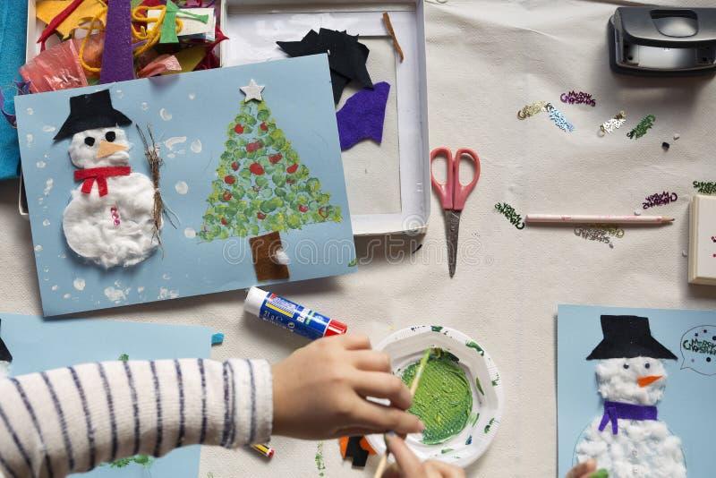 Handen van een 10 éénjarigenmeisje die een Kerstmisambacht doen stock fotografie