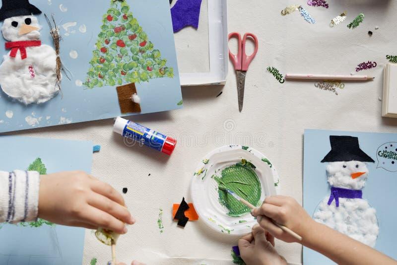 Handen van een 10 éénjarigenmeisje die een Kerstmisambacht doen stock afbeeldingen