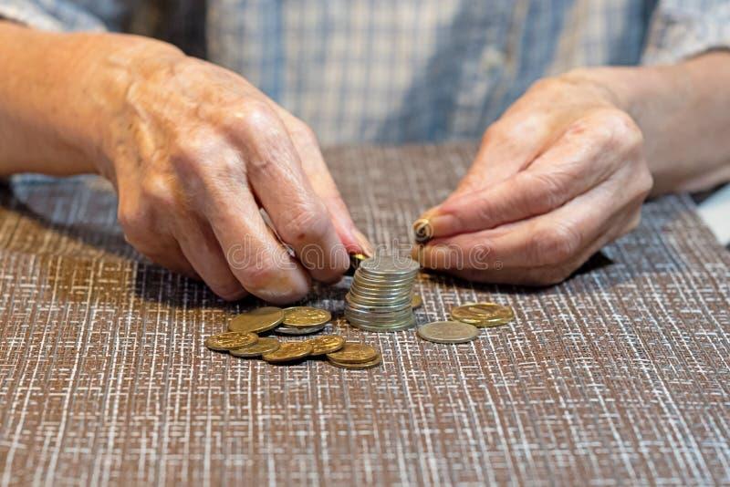 Handen van een bejaarde en muntstukken voor redding Het concept besparingsgeld Close-up stock afbeeldingen