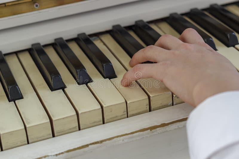 Handen van een jong meisje die op een witte piano, close-up spelen stock fotografie