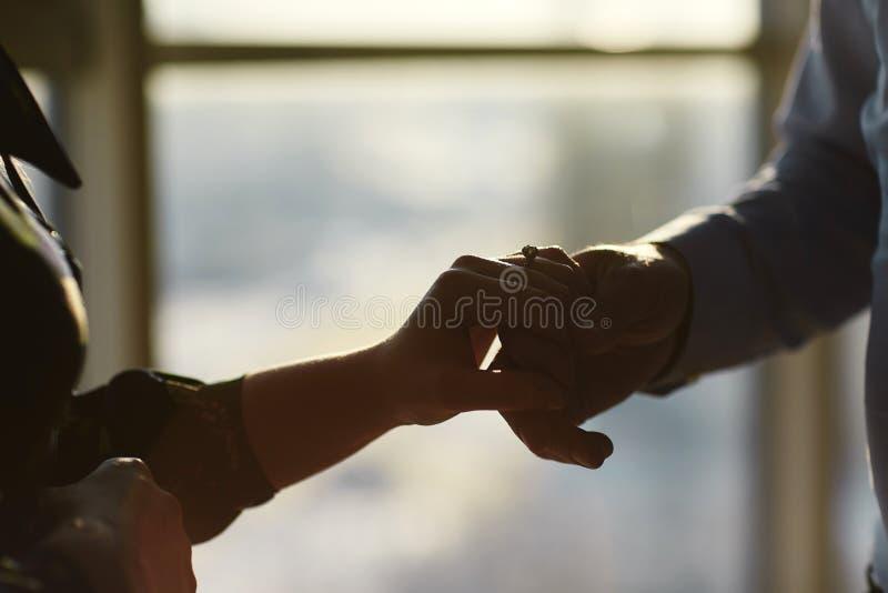 Handen van een jong paar met een ring Sluit omhoog van de mens die diamantring geven aan vrouw royalty-vrije stock fotografie