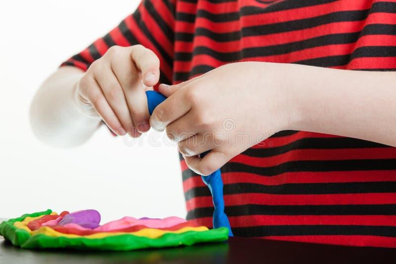 Handen van een jonge jongen die met plastic stopverf spelen royalty-vrije stock afbeelding