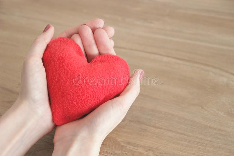 Handen van een jonge mooie vrouw die zacht een rood hart houden, op een houten achtergrond, selectieve nadruk, sparen ruimte royalty-vrije stock fotografie