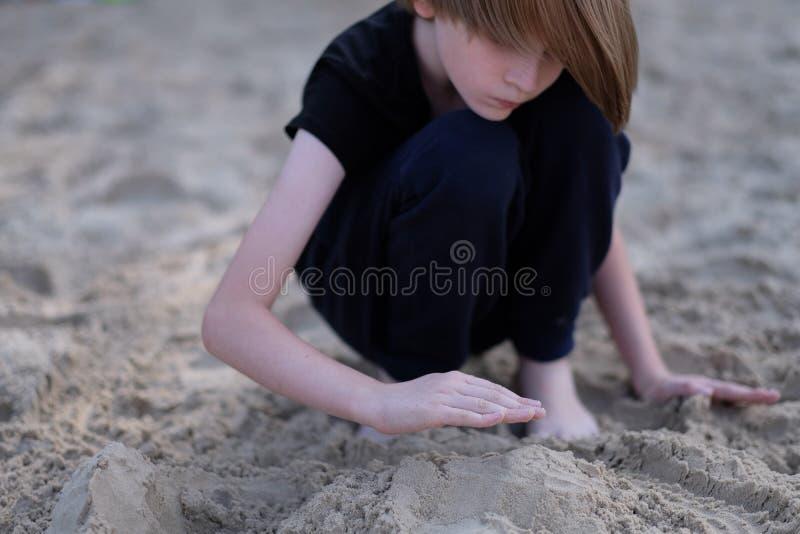 Handen van een jongen die in het natte zand spelen royalty-vrije stock afbeeldingen