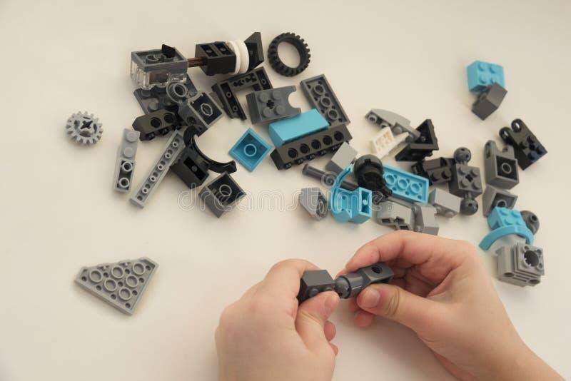Handen van een kind dat van de details van de ontwerper op een witte achtergrond bouwt stock afbeelding