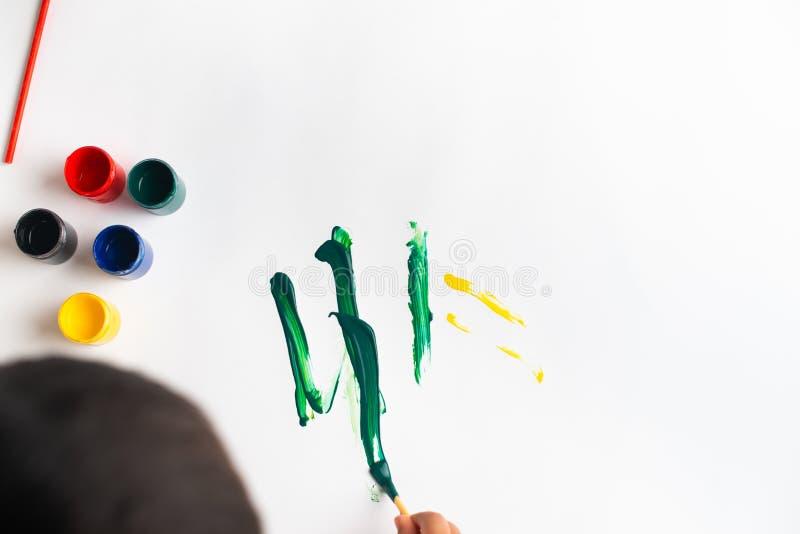 Handen van een kleine jongen die met waterverf op Witboekblad schilderen Weinig jongen met een borstel en verven Terug naar het C stock foto's
