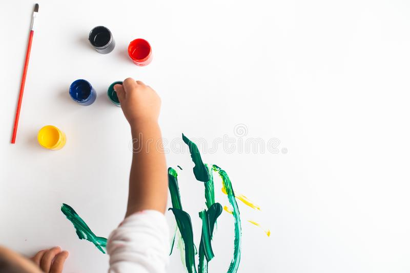 Handen van een kleine jongen die met waterverf op Witboekblad schilderen Weinig jongen met een borstel en verven Terug naar het C royalty-vrije stock afbeelding
