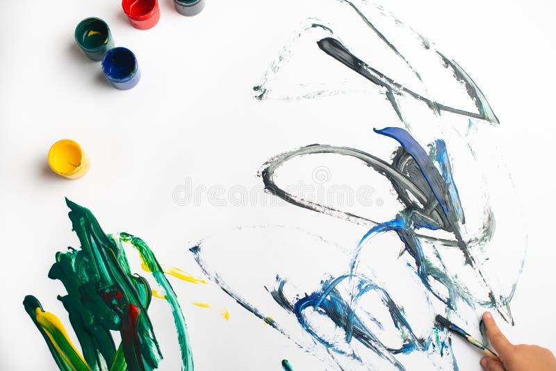 Handen van een kleine jongen die met waterverf op Witboekblad schilderen Weinig jongen met een borstel en verven Terug naar het C royalty-vrije stock foto's