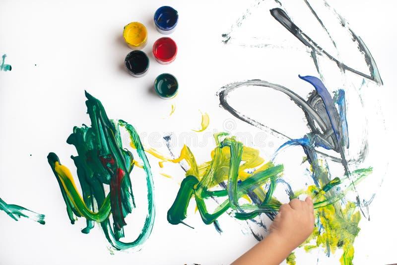 Handen van een kleine jongen die met waterverf op Witboekblad schilderen Weinig jongen met een borstel en verven Terug naar het C stock afbeelding