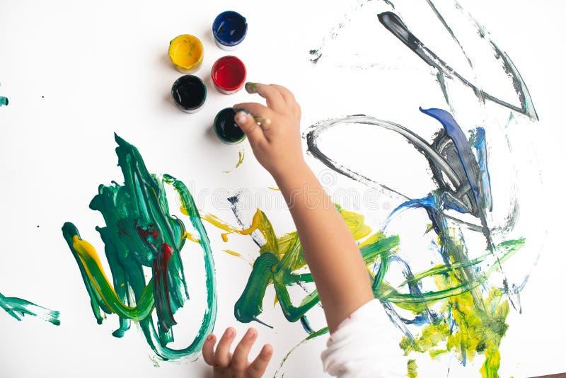 Handen van een kleine jongen die met waterverf op Witboekblad schilderen Weinig jongen met een borstel en verven Terug naar het C royalty-vrije stock foto