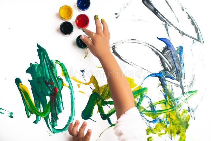 Handen van een kleine jongen die met waterverf op Witboekblad schilderen Weinig jongen met een borstel en verven Terug naar het C stock fotografie